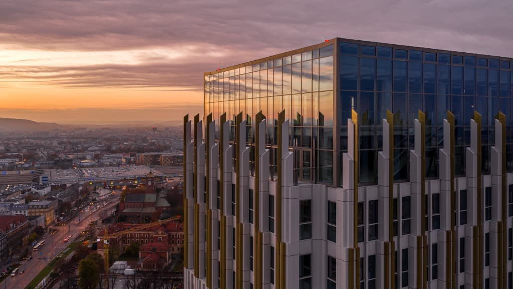 Kadr z ujęć filmowych z drona na biurowiec Unity Centre w Krakowie o zachodzie słońca. W tle wyłania się Dworzec Główny wraz z Galerią Krakowską.