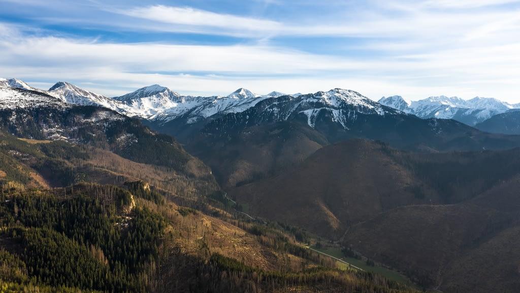 Fotografia z drona na Tatry. Ośnieżone szczyty gór, a poniżej dolne partie zaczynają się zielenić