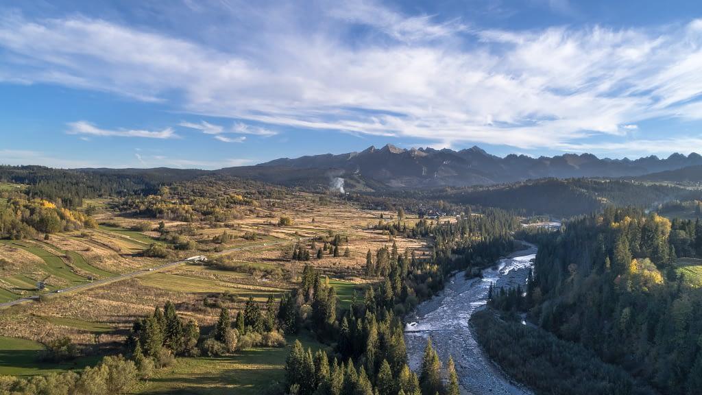 Zdjęcie z powietrza z widokiem na Tatry, Podhale. Rzeka płynąca pomiędzy drzewami, a obok połacie ziemi uprawnej.