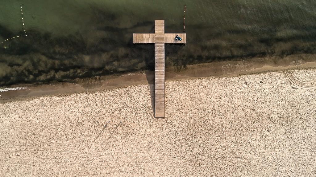 Zdjęcie z lotu ptaka nad morzem w Sopocie. Widoczne molo w kształcie krzyża i leżąca na nim kobieta z dzieckiem oraz plaża i morze.