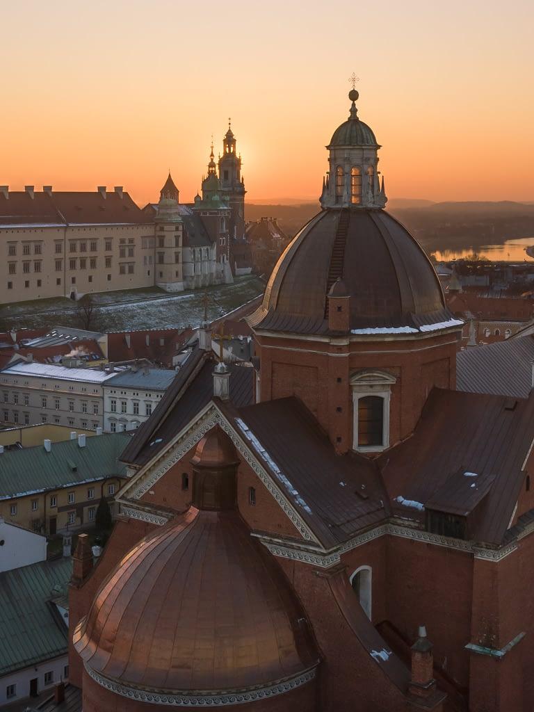 Wieża kościoła, a w tle Wawel. Zdjęcie z drona o zachodzie słońca.
